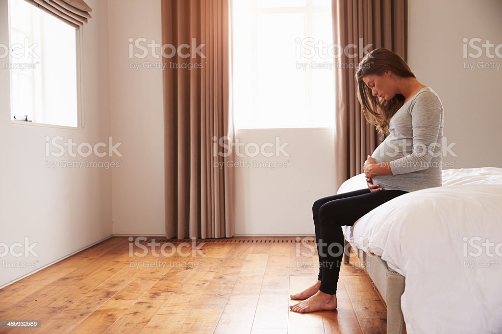 Pregnant Woman Sitting On Bed Holding Belly stock photo