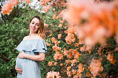 Pregnant woman standing next to flowers