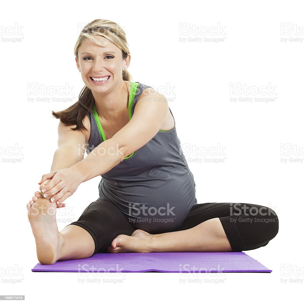 Pregnant woman stretching legs on exercise mat stock photo
