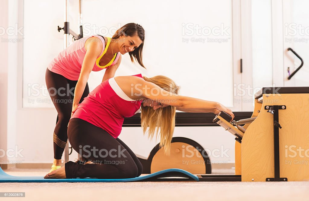 Pregnant woman stretching on Pilates chair with help of instructor. stock photo