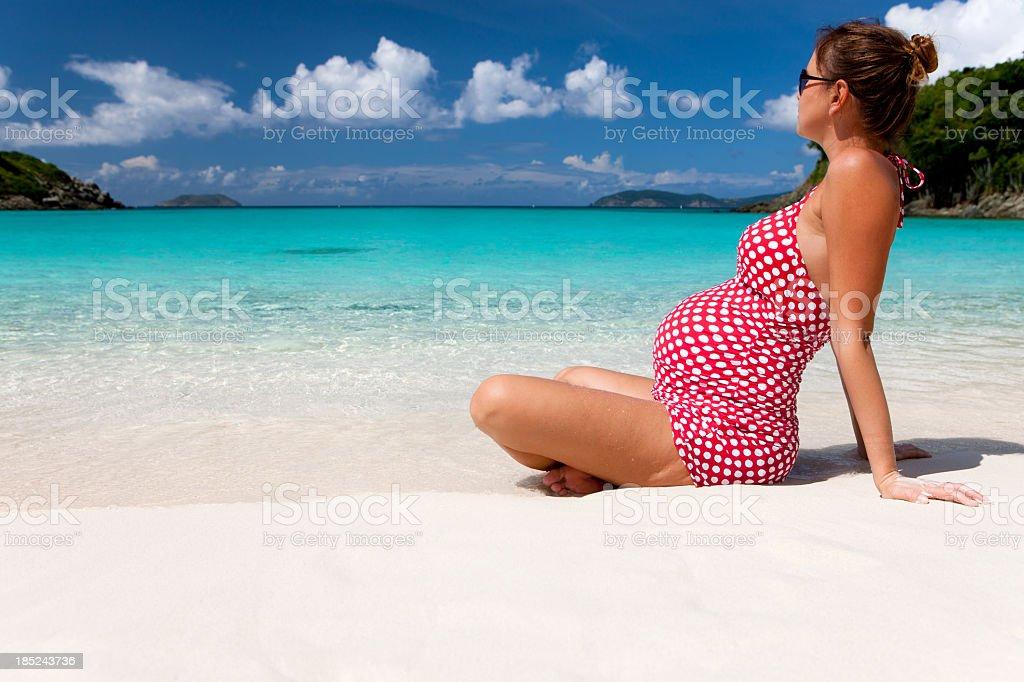 pregnant woman sunbathing at a Caribbean beach stock photo