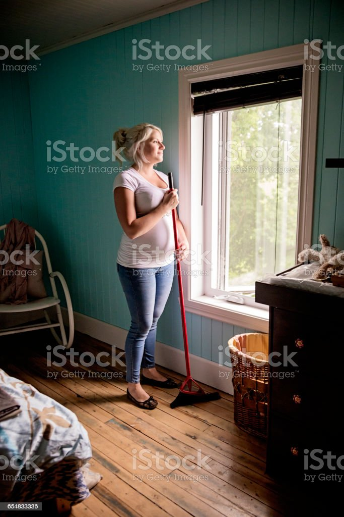 Pregnant woman sweeping the floor in home bedroom. stock photo