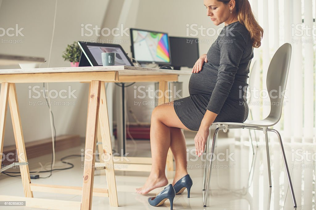 Pregnant woman taking off her shoes stock photo