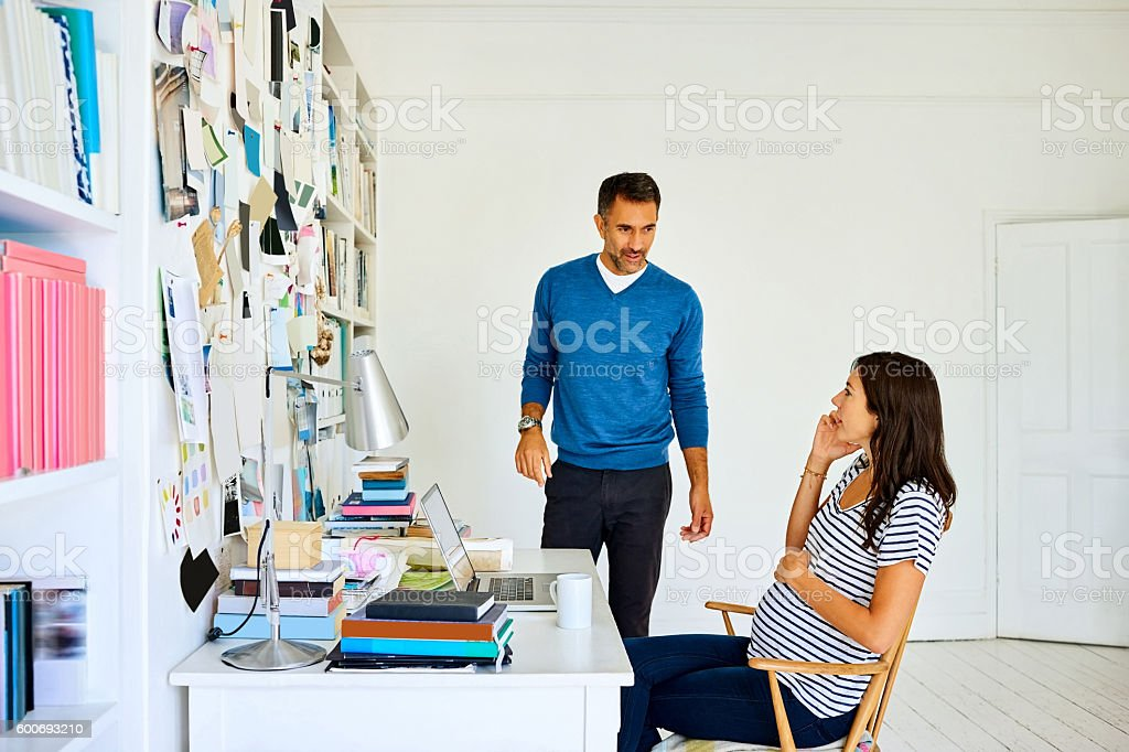 Pregnant woman talking on mobile phone with husband stock photo