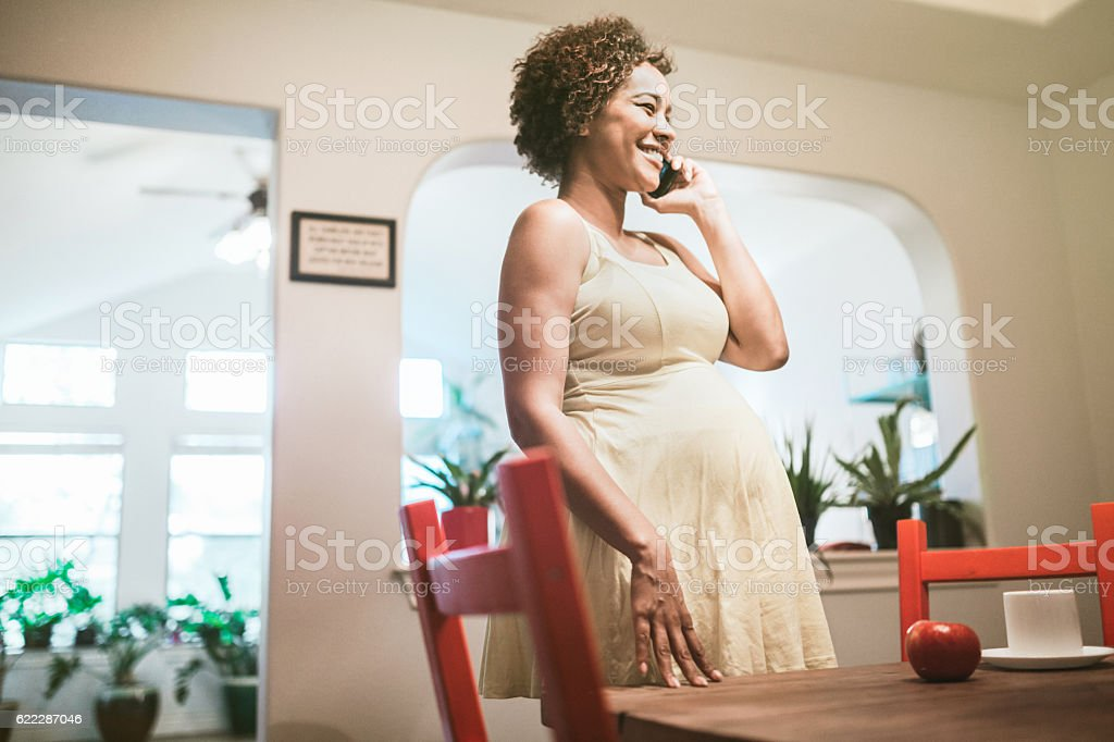 Pregnant Woman Talking on Smart Phone stock photo