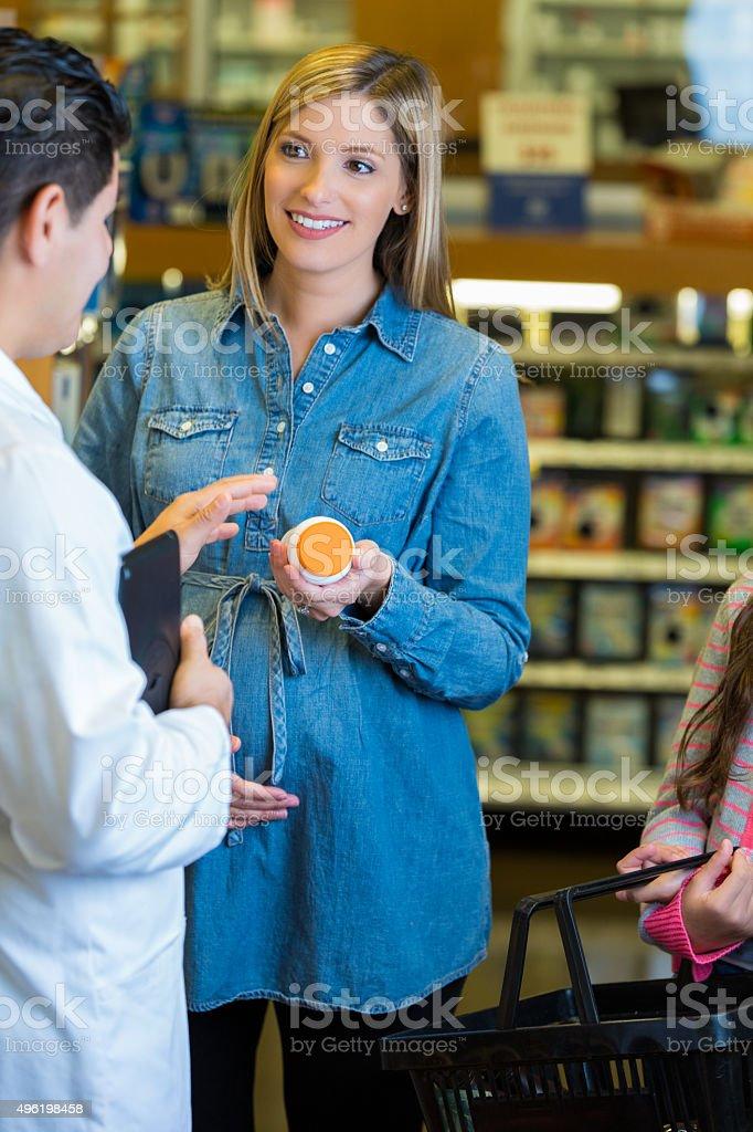 Pregnant woman talking to pharmacist about prenatal vitamins stock photo
