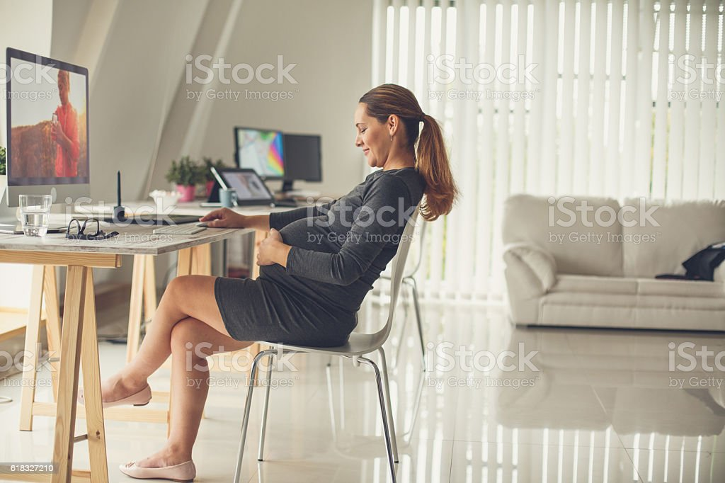 Pregnant woman touching her belly in the office stock photo