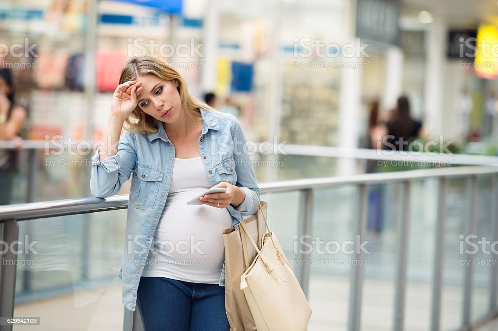 Pregnant woman touching her forehead, having headache stock photo