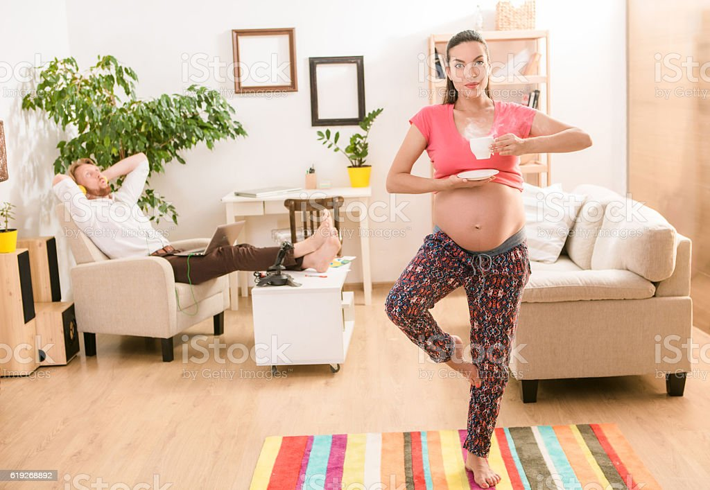 Pregnant woman training at home stock photo