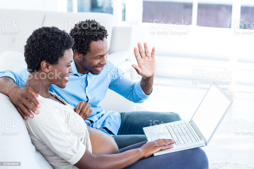 Pregnant woman using laptop while sitting by husband royalty-free stock photo