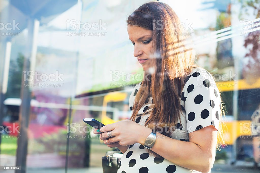 Pregnant woman using phone on station. stock photo