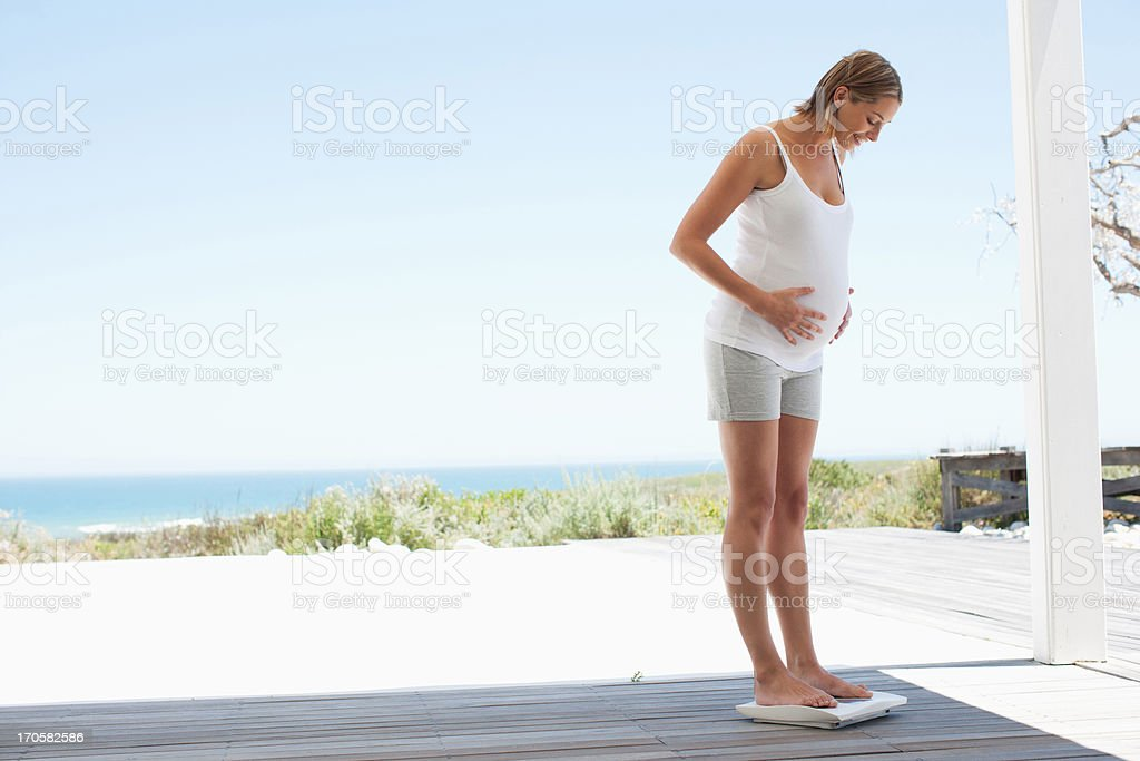 Pregnant woman weighing herself royalty-free stock photo
