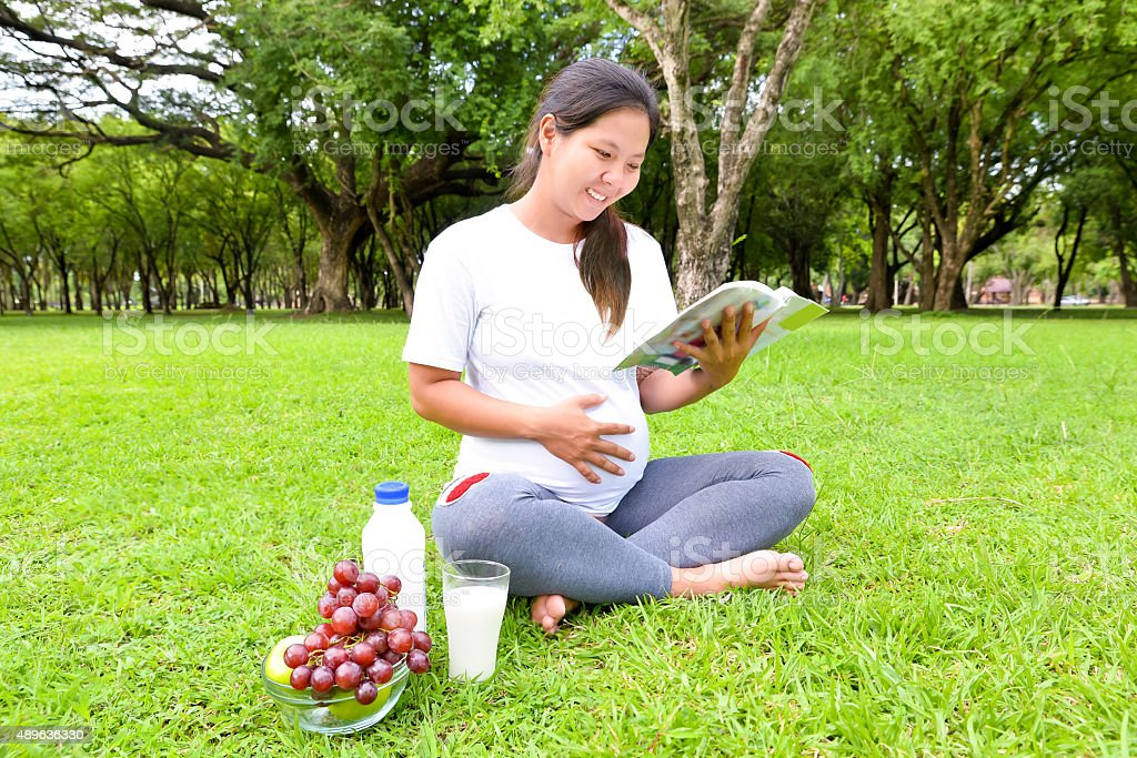 Pregnant woman with baby book and food stock photo