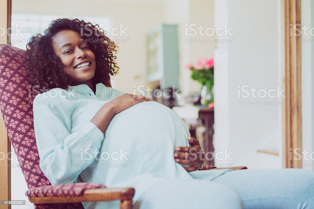 Pregnant woman with hands on stomach at home stock photo