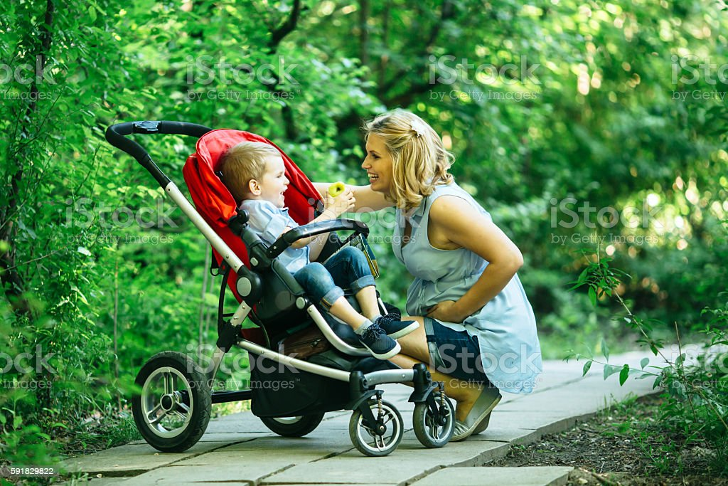 Pregnant woman with her child in pram stock photo