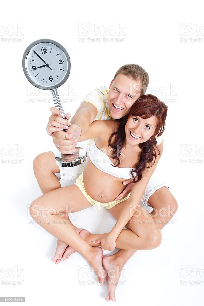 Pregnant woman with husband, holding a clock showing 9th month. royalty-free stock photo