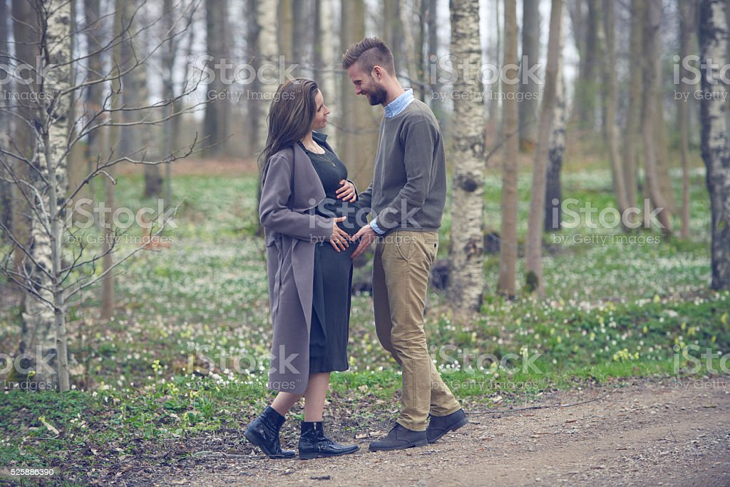Pregnant woman with husband standing  outdoor in forest stock photo