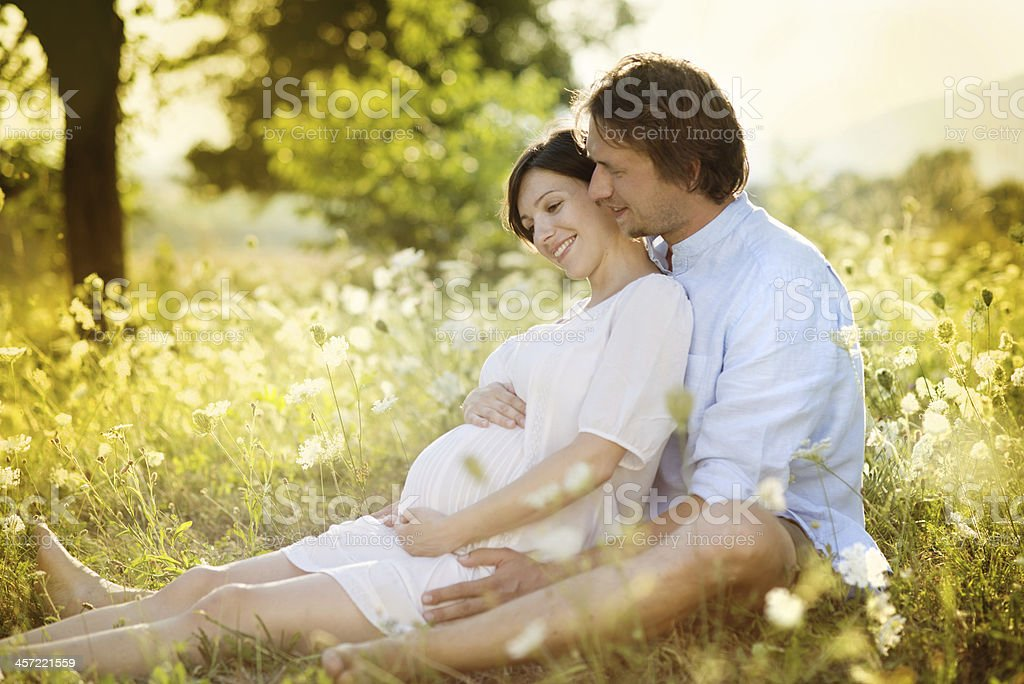 Pregnant woman with man in field stock photo