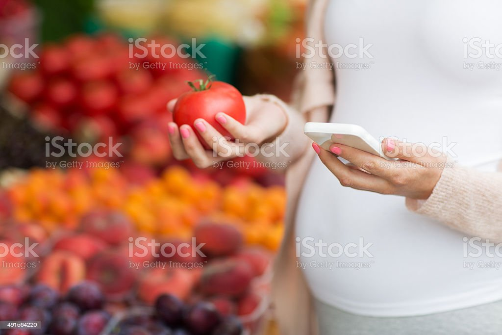 pregnant woman with smartphone at street market stock photo