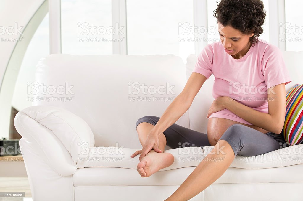 Pregnant woman with swollen feet and leg pain stock photo
