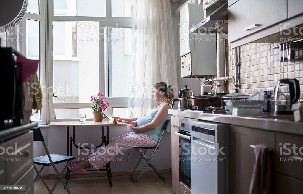 Pregnant woman working in kitchen. stock photo