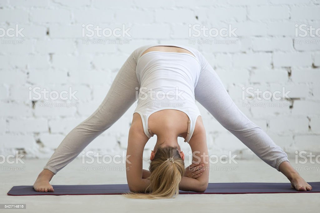 Pregnant woman working out, doing yoga pose stock photo