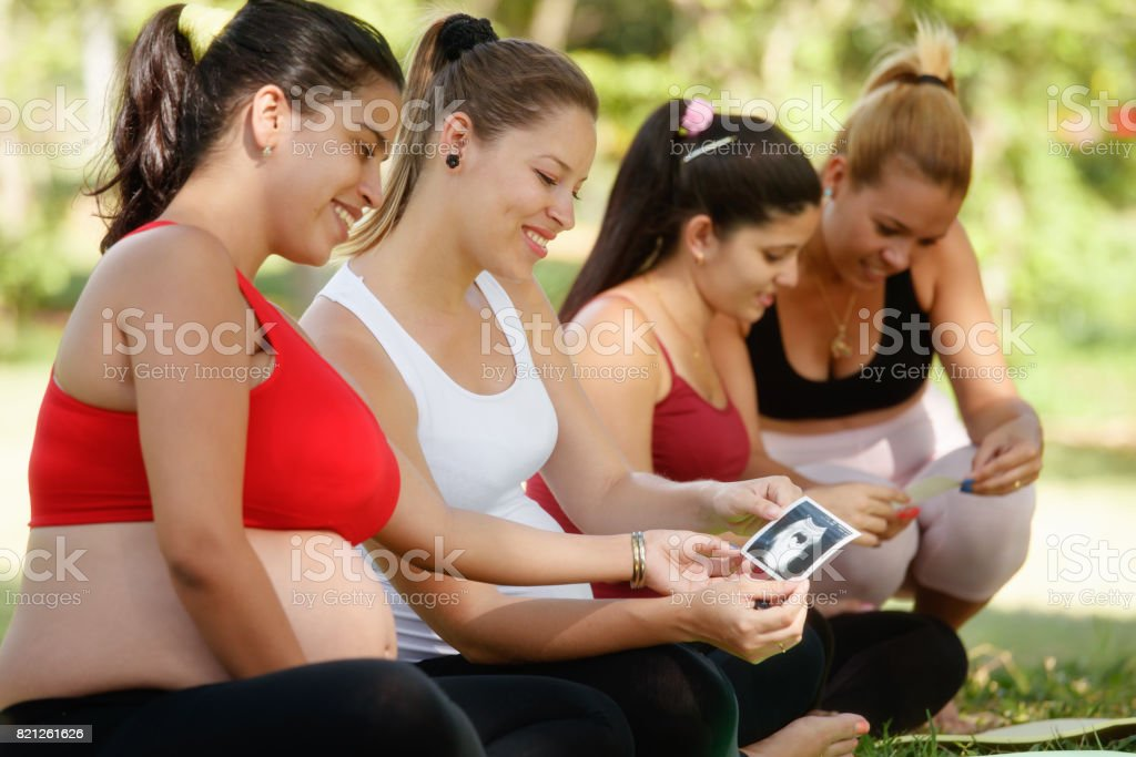 Pregnant Women Sharing Ecography Images In Prenatal Class stock photo