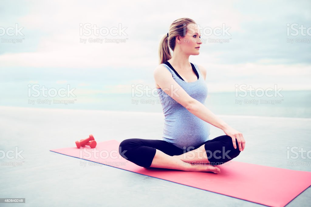Pregnant young woman doing fitness exercises stock photo