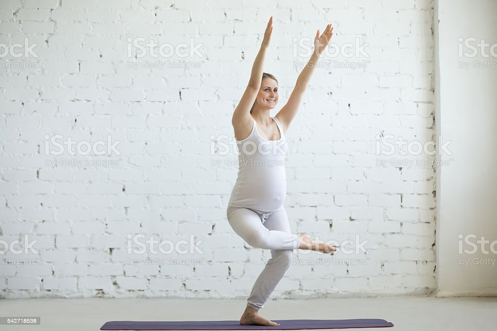 Pregnant young woman doing prenatal yoga. Chair Pose, Utkatasana stock photo