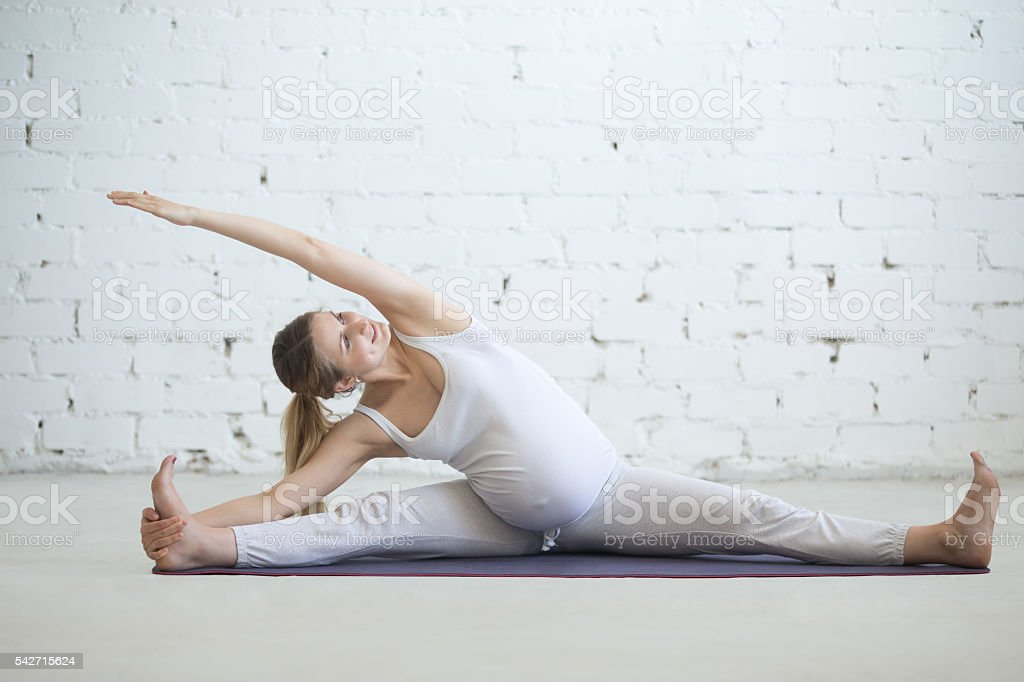 Pregnant young woman doing prenatal yoga. Side bend stock photo