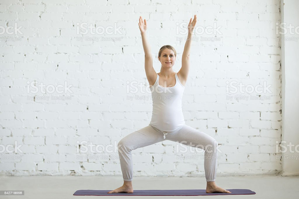 Pregnant young woman doing prenatal yoga. Sumo Squat Pose stock photo