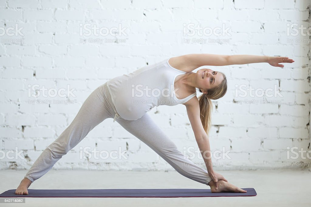 Pregnant young woman doing prenatal yoga. Utthita Trikonasana po stock photo