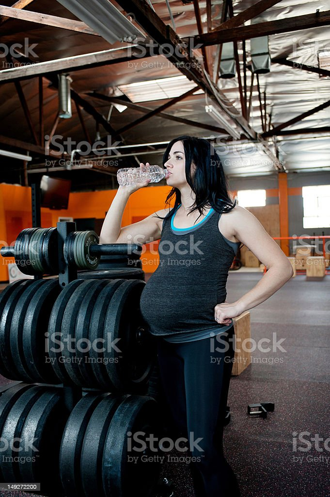 Pregnant young woman drinking mineral water stock photo