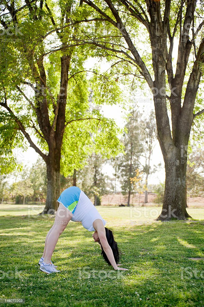 Pregnant young woman in downward facing dog position stock photo