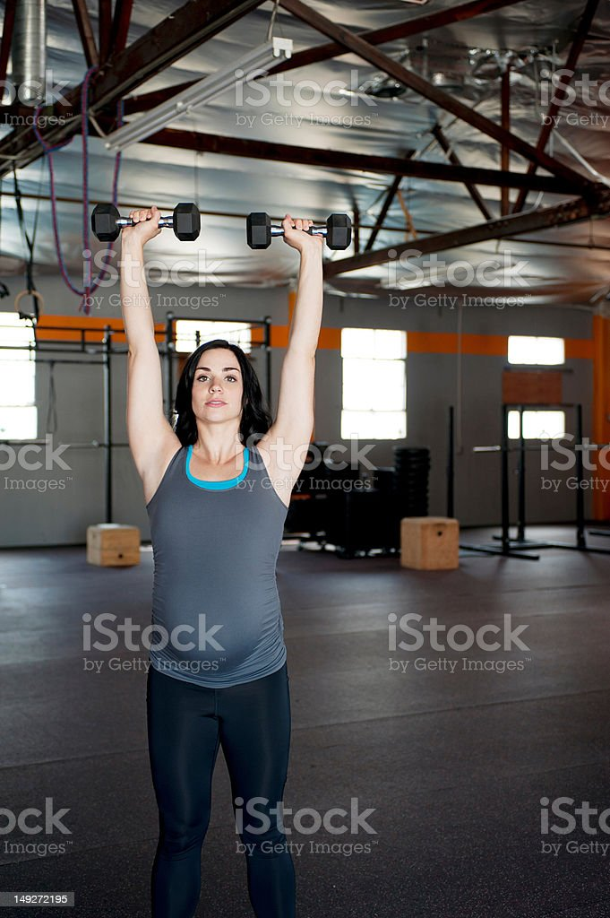 Pregnant young woman with hand weights stock photo