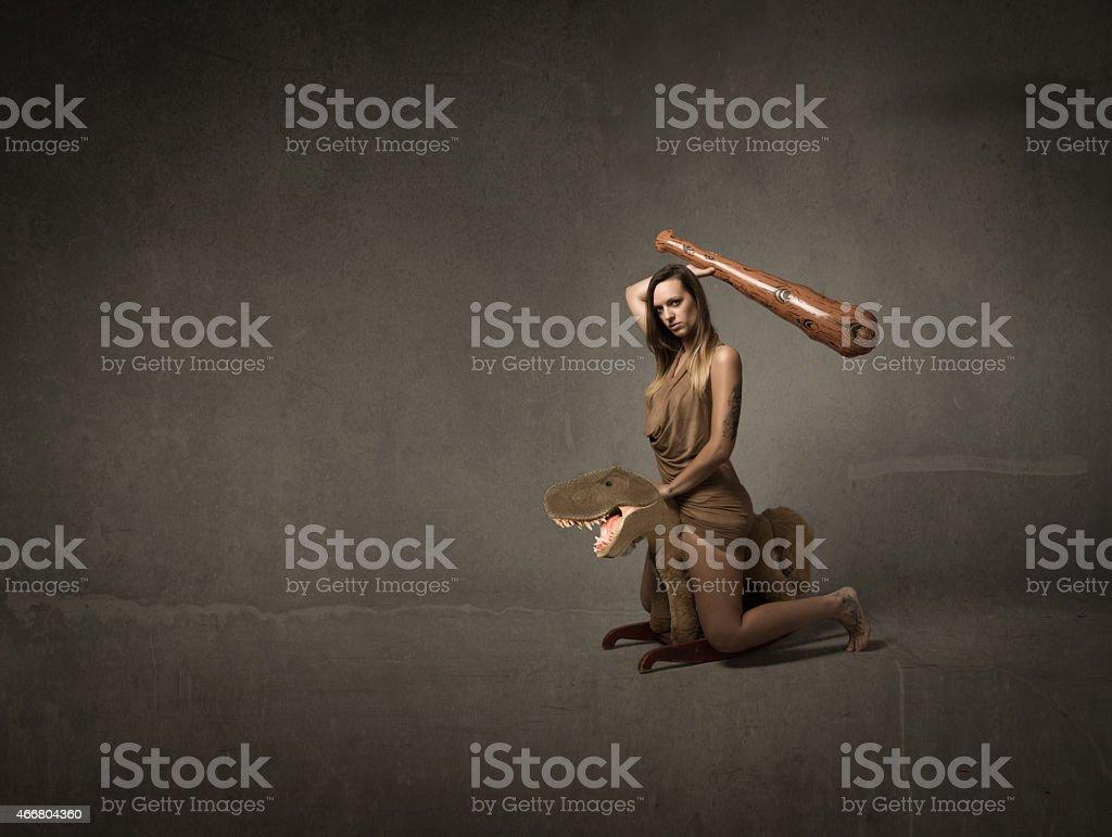 prehistoric girl riding a dinosaur stock photo