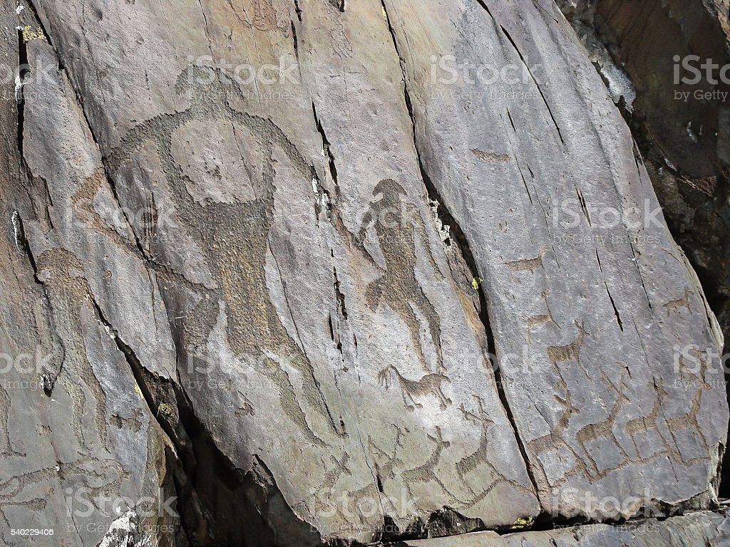 Prehistorical people and animals petroglyphs carved in stones stock photo