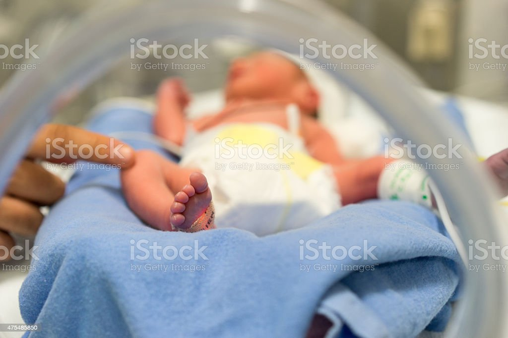 Premature baby and hand of the doctor stock photo