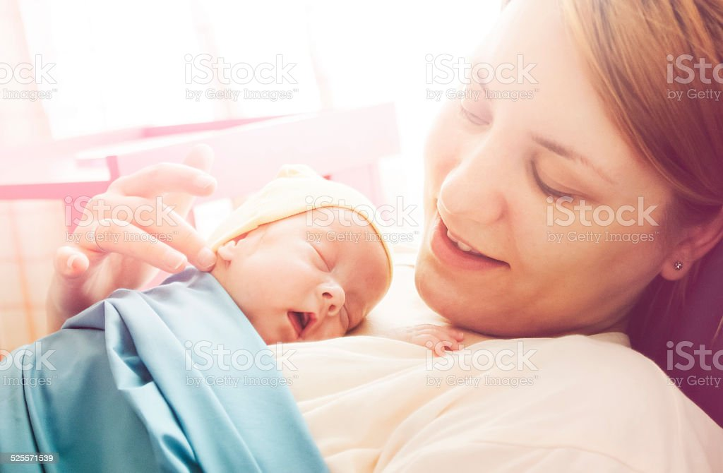 Premature baby girl resting on mother's breasts stock photo