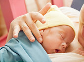 Premature baby resting in mother's arms