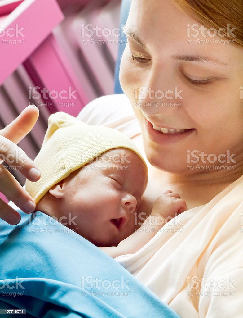 Premature baby sleeping in mother's arms stock photo