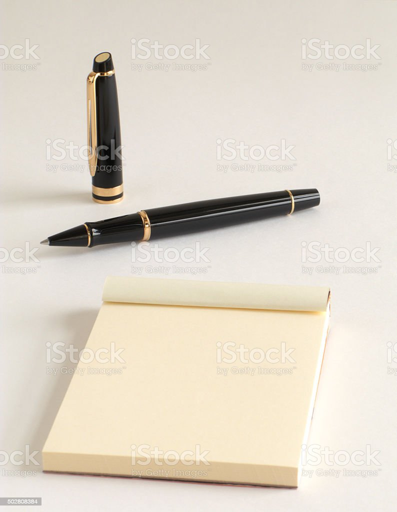 Premium, Gold-plated, black lacquered rollerball pen with a writing pad stock photo