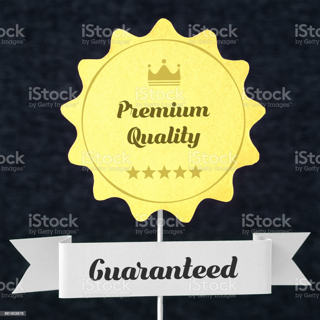 Premium quality guaranteed badge cut from cardboard and paper on a wooden stick. Yellow banner and ribbon for business website to promise customer the best product or service. Seal on dark background. stock photo