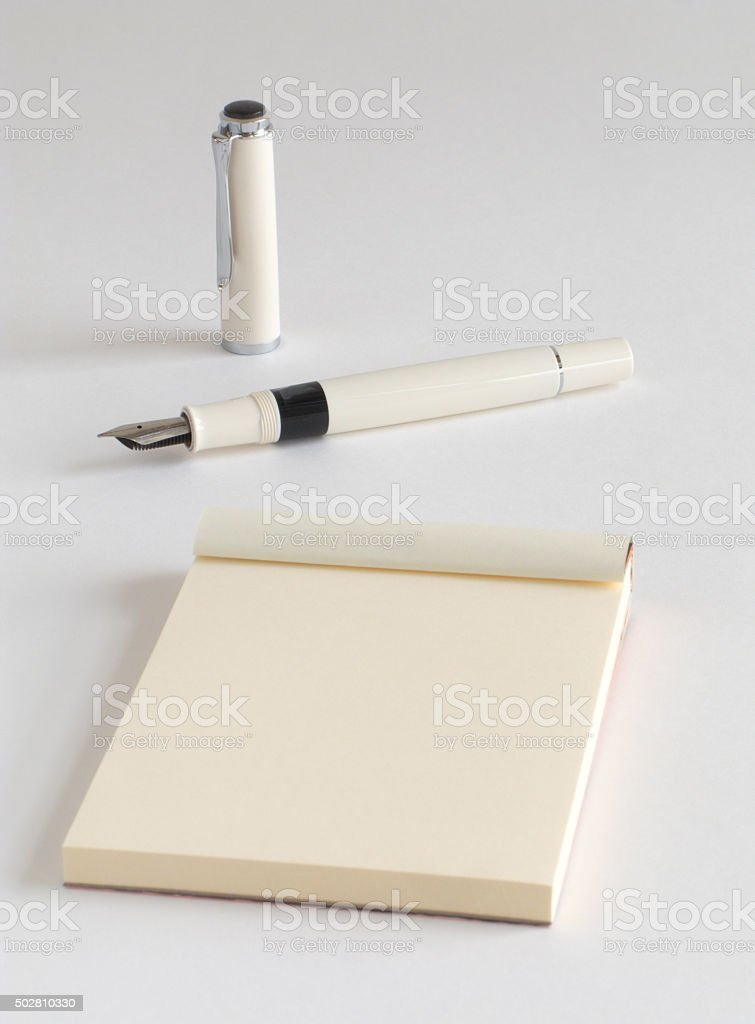 Premium white lacquered fountain pen with a writing pad stock photo