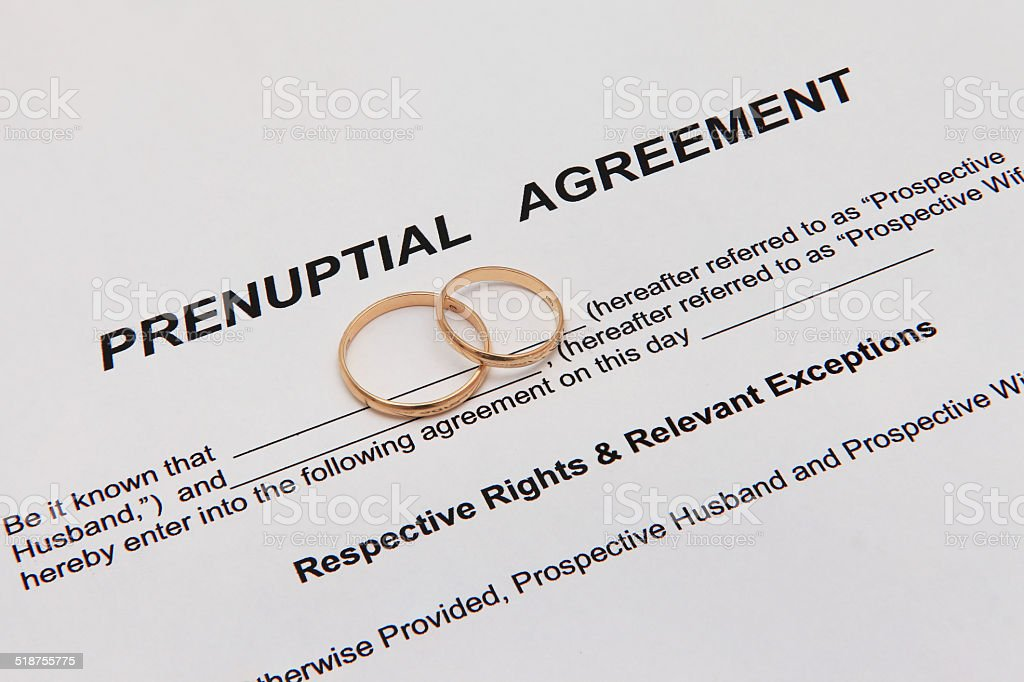 Prenuptial Agreement form and two gold wedding rings stock photo