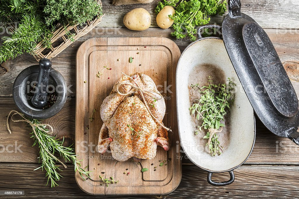 Preparation for roasting chicken with herbs stock photo