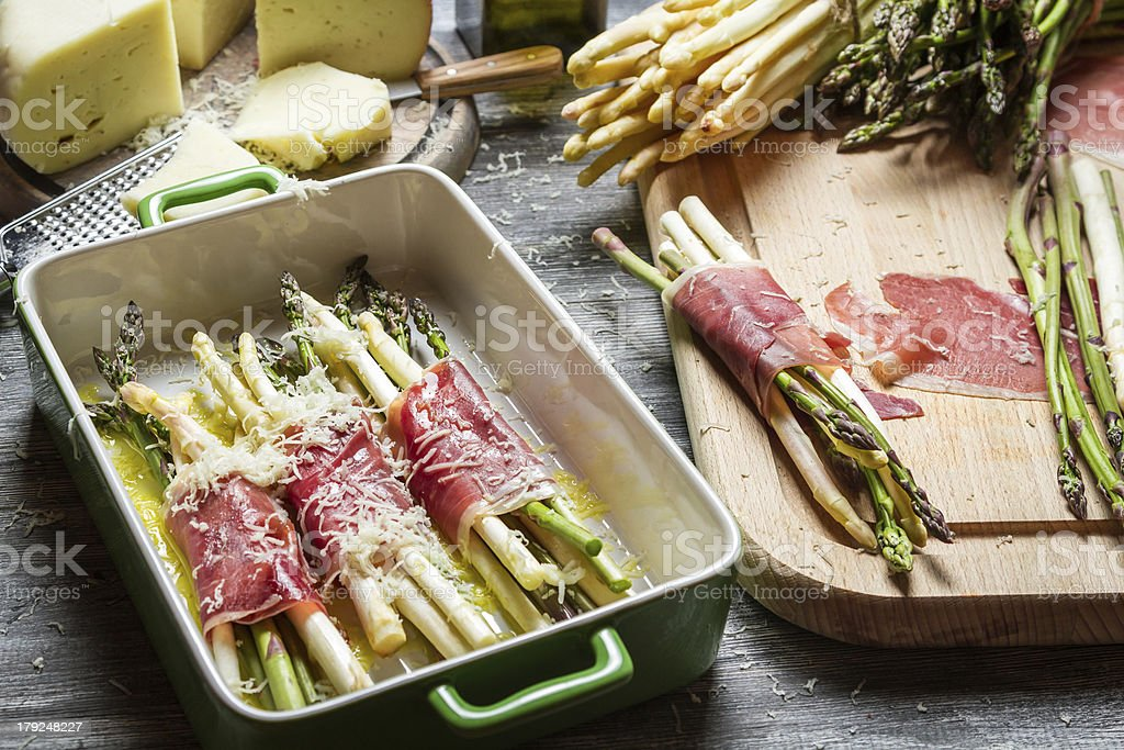 Preparation of asparagus wrapped in Parma ham with cheese royalty-free stock photo