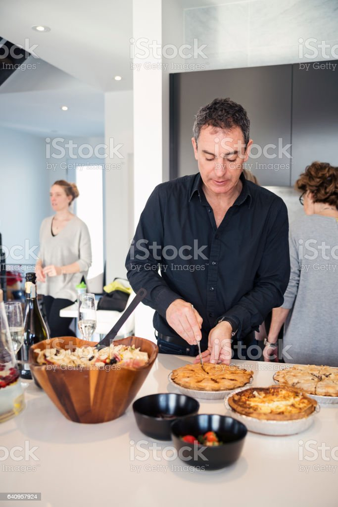Preparation of big family dinner, people busy at kitchen counter. stock photo