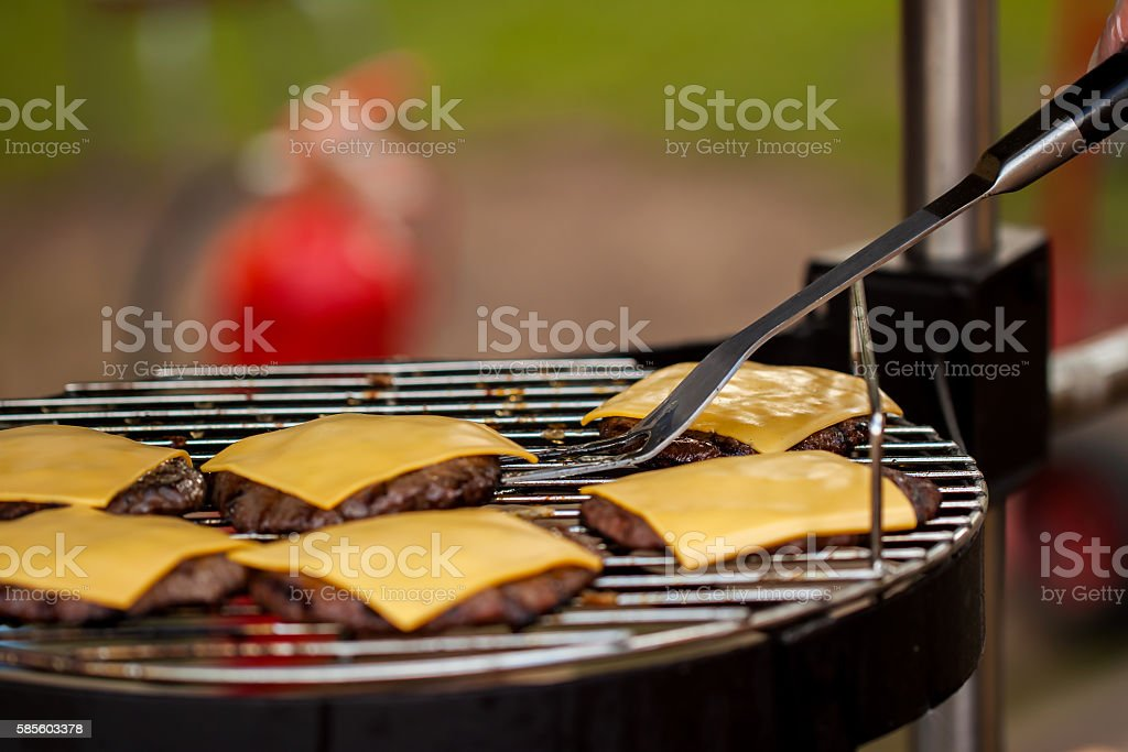 Preparation of cheeseburgers on family BBQ day stock photo