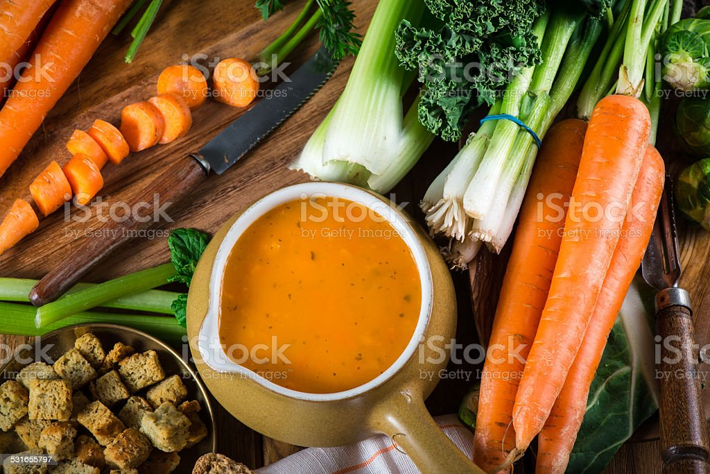 Preparation of fresh creamy carrot soup stock photo